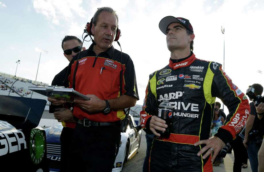 Jeff Gordon, right, watches the scoreboard as he talks to a crew member during qualifying at the Richmond International Raceway in Richmond, Va., Friday, Sept. 6, 2013. Gordon won the pole for Saturday night's NASCAR Sprint Cup race. (AP Photo/Steve Helber) ORG XMIT: VASH104 Photo: Steve Helber / AP