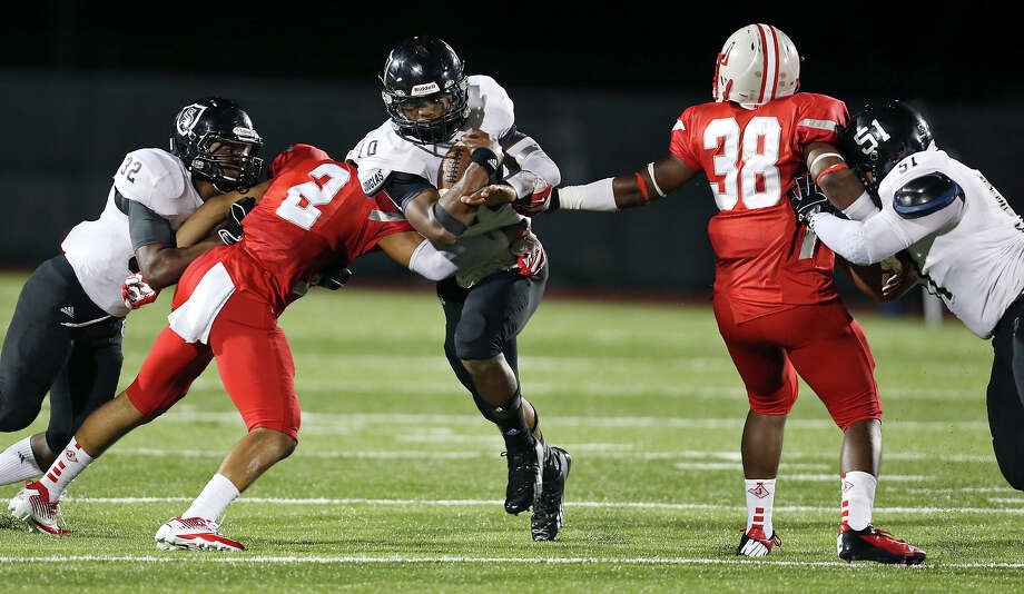 Steele's L.G. Williams (center) looks for room between Judson's Shawn Calvin (center left) and Rashawn Pickens as Steele's Keshawn Brown (left) and J.P. Fernandez block during second half action Friday Sept. 6, 2013 at D.W. Rutledge Stadium. Steele won 51-34. Photo: Edward A. Ornelas, San Antonio Express-News / © 2012 San Antonio Express-News