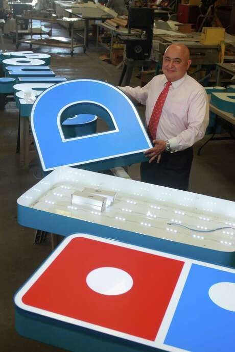 Joe Minavi of Sparkle Sign Co., with a Domino Pizza sign that is in production. Photo: Gary Fountain, Freelance / Copyright 2013 Gary Fountain.