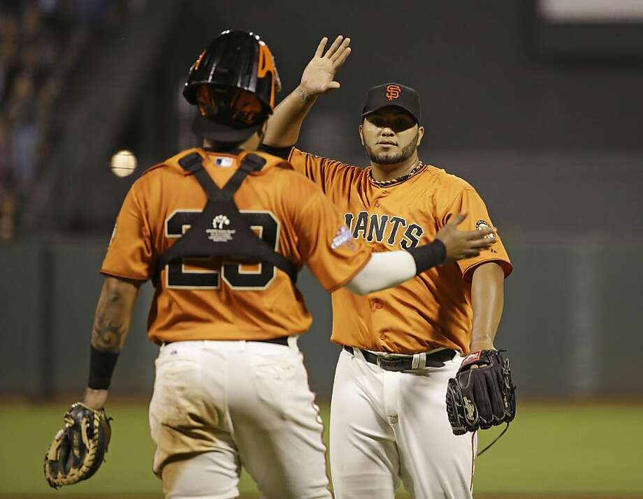 Yusmeiro Petit, right, is greeted by catcher Hector Sanchez, left, at the end of a game against the Arizona Diamondbacks in September 2013 in San Francisco. Photo: Eric Risberg, Associated Press