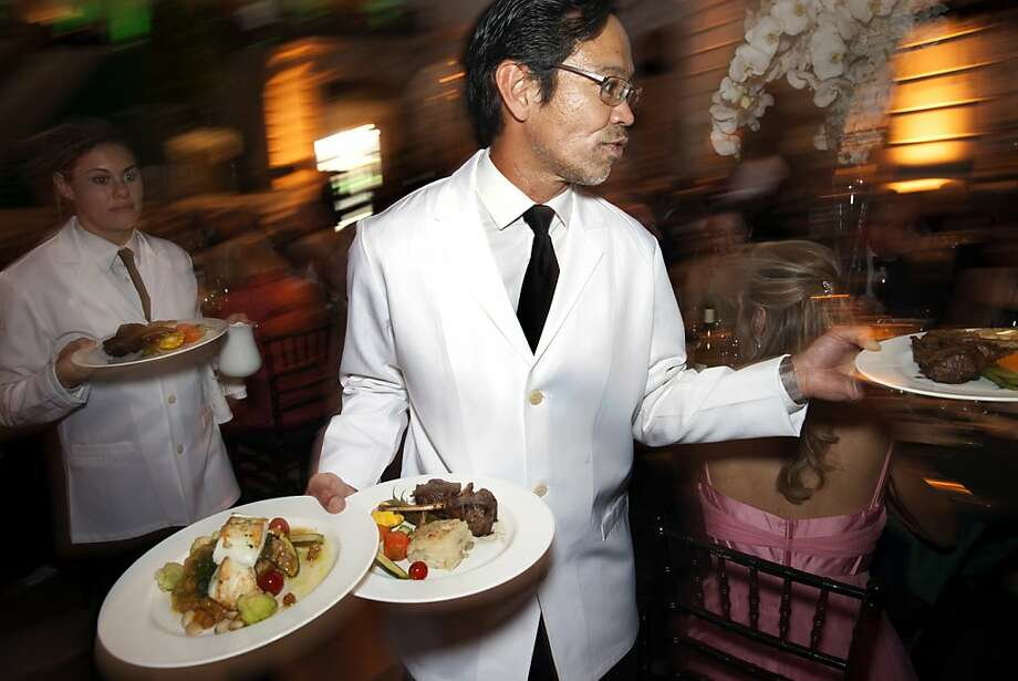 Larry Arakaki serves lamb chops and fish to dinner guests at the 91st San Francisco Season-Opening Opera Gala in San Francisco Calif. on Friday, Sept. 6, 2013. Photo: Alex Washburn, Special To The Chronicle