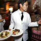 Larry Arakaki serves lamb chops and fish to dinner guests at the 91st San Francisco Season-Opening Opera Gala in San Francisco Calif. on Friday, Sept. 6, 2013.