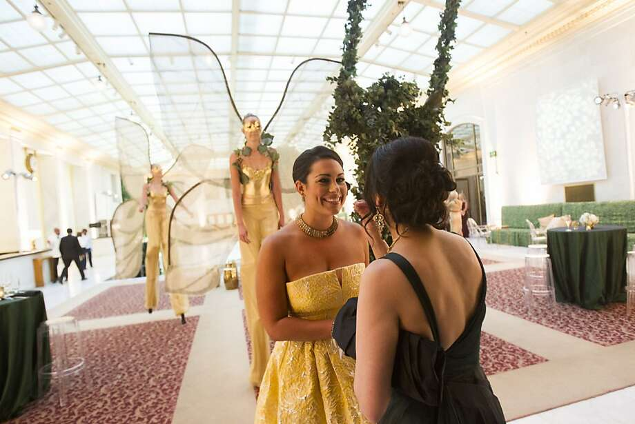 Libby Leffler (left) and Bilques Smith converse at the gala as strange and mysterious oddities drift behind them through City Hall's graceful spaces. Photo: Stephen Lam, Special To The Chronicle