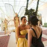 Libby Leffler (left) and Bilques Smith converse at the gala as strange and mysterious oddities drift behind them through City Hall's graceful spaces.