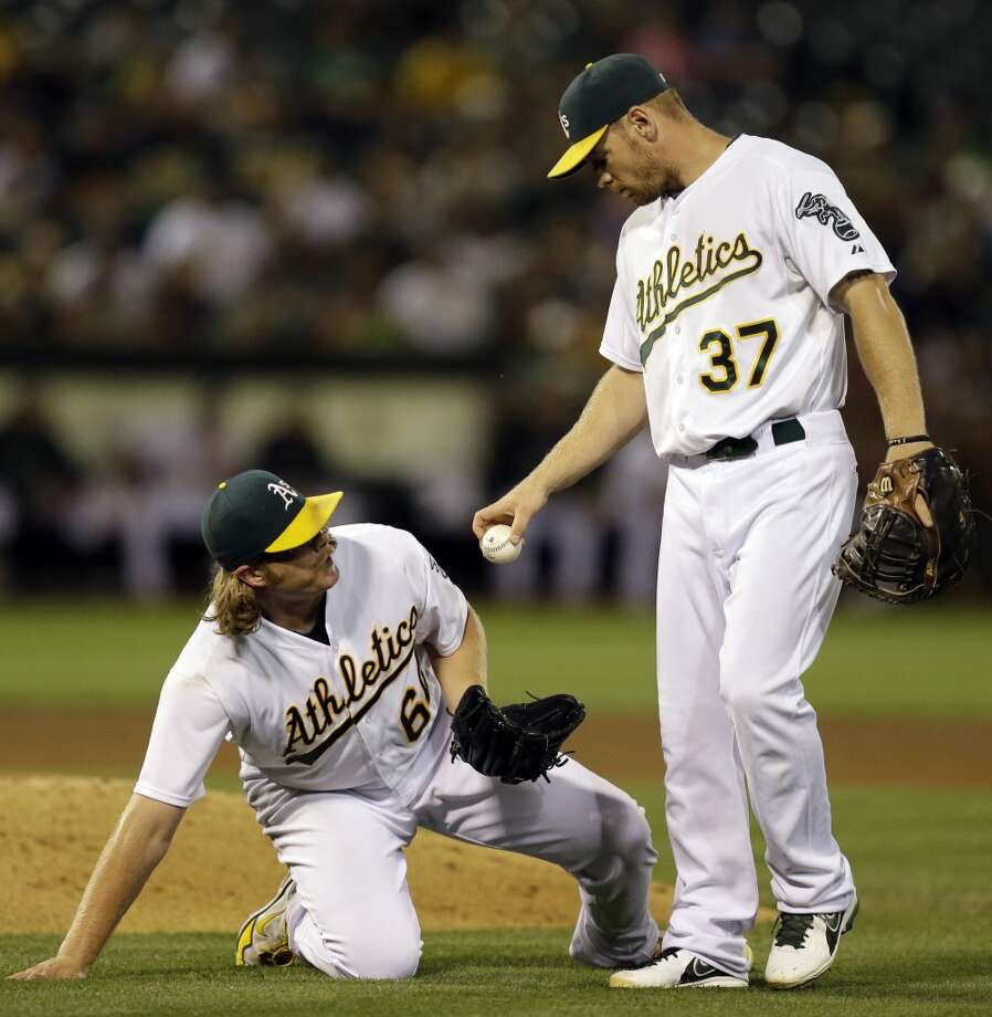 Brandon Moss, right, returns the ball to pitcher A.J. Griffin in the fourth inning. Photo: Ben Margot, Associated Press