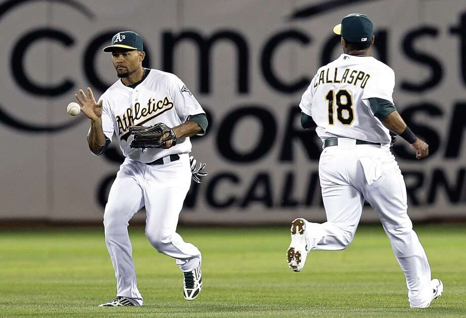 Coco Crisp, left, and Alberto Callaspo (18) cannot make the catch on a single hit by Trevor Crowe. Photo: Ben Margot, Associated Press
