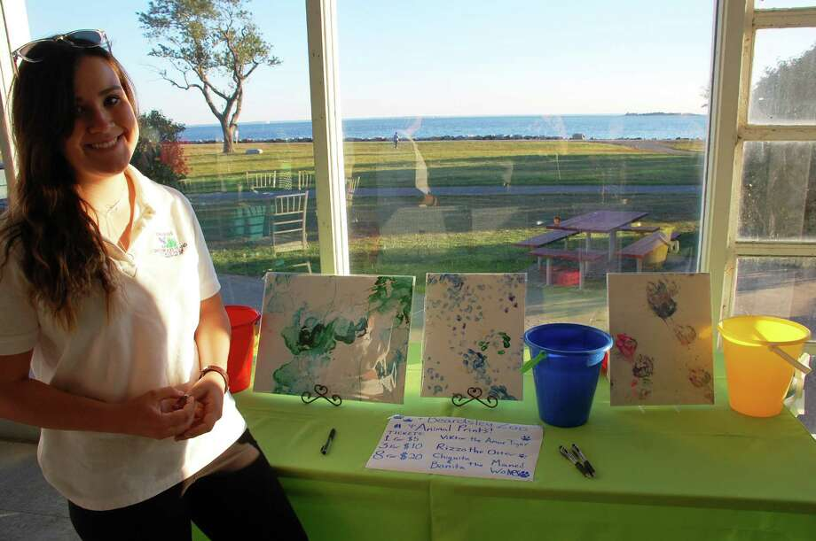 "At the Sherwood Island Shorefest on friday, Alex Purcell, 17, of Westport, shows off ""artwork"" by some Beardsley Zoo residents, including Viktor the tiger, Rizzo the otter, and Ciquita and Bonita, two maned wolves. Photo: Jarret Liotta / Westport News contributed"