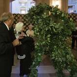 Jim Oakes, left, and Arlene Inch laugh as they're surpassed by a moving bush performer during the 91st Season Opening Night Gala of the San Francisco Opera at City Hall in San Francisco, Calif. on Friday, Sept. 6, 2013.