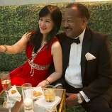 Nina Belle, in lipstick red with sparkling trim, takes a selfie with Charles Belle at the gala.