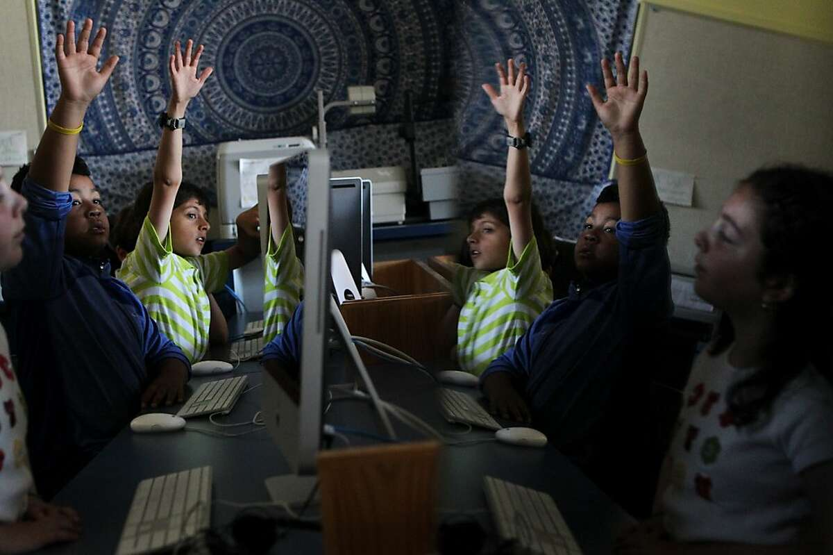 From left, students Emma Gorin, 9, Antonio Harris, 9, and Shahzaib Mirza, 9, are reflected on a sleeping screen as they answer questions on a practice test during fourth grade computer class September 5, 2013 at Argonne Elementary School in San Francisco, Calif. Argonne students are preparing for the state and district's transition to computerized testing by practicing keyboarding and taking practice standardized tests.