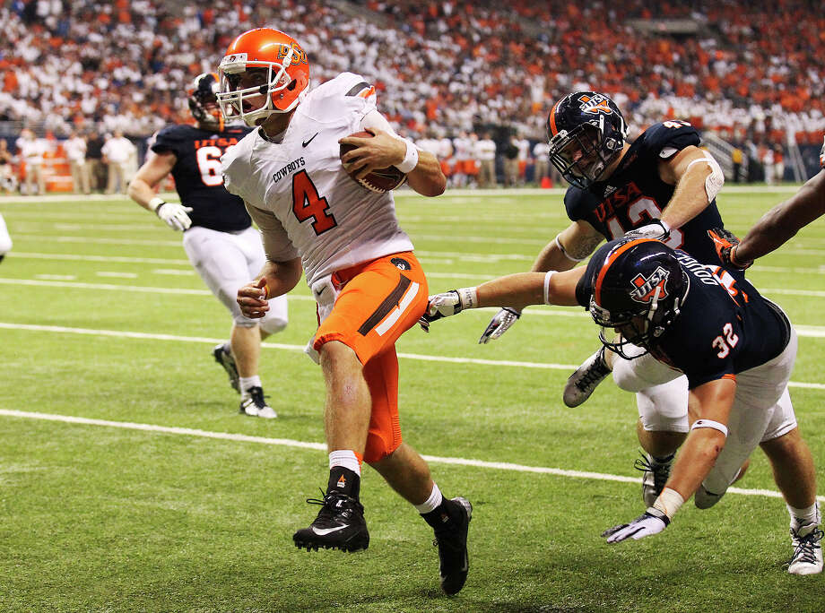 Oklahoma State's J.W. Walsh (04) scores a touchdown in the first half against UTSA at the Alamodome on Saturday, Sept. 7, 2013. Photo: Kin Man Hui, San Antonio Express-News / ©2013 San Antonio Express-News