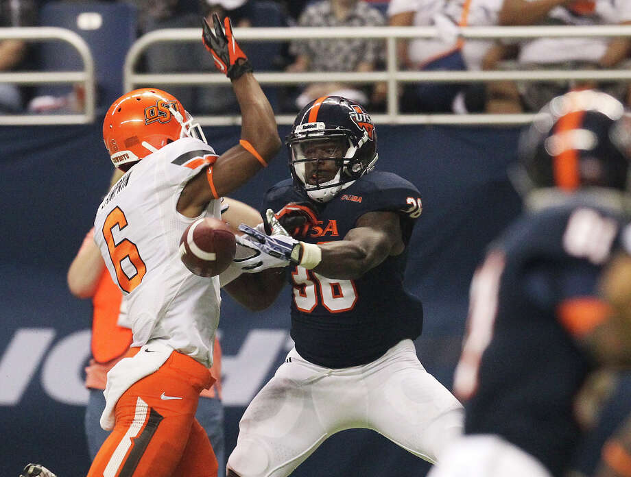 UTSA's Evans Okotcha (36) struggles for a catch against Oklahoma State's Ashton Lampkin (06) in the first half at the Alamodome on Saturday, Sept. 7, 2013. Photo: Kin Man Hui, San Antonio Express-News / ©2013 San Antonio Express-News