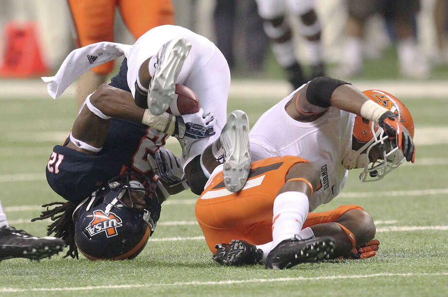 UTSA's Earon Holmes (12) gets turned upside down after catch against Oklahoma State's Kevin Peterson (01) in the first half at the Alamodome on Saturday, Sept. 7, 2013. Photo: Kin Man Hui, San Antonio Express-News / ©2013 San Antonio Express-News