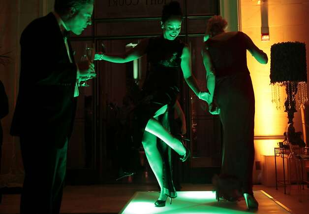 Michelle Molfino (center) and Lori Shigekane step out on a glowing green-lit dance platform at the Opera gala's after-party. Photo: Alex Washburn, Special To The Chronicle