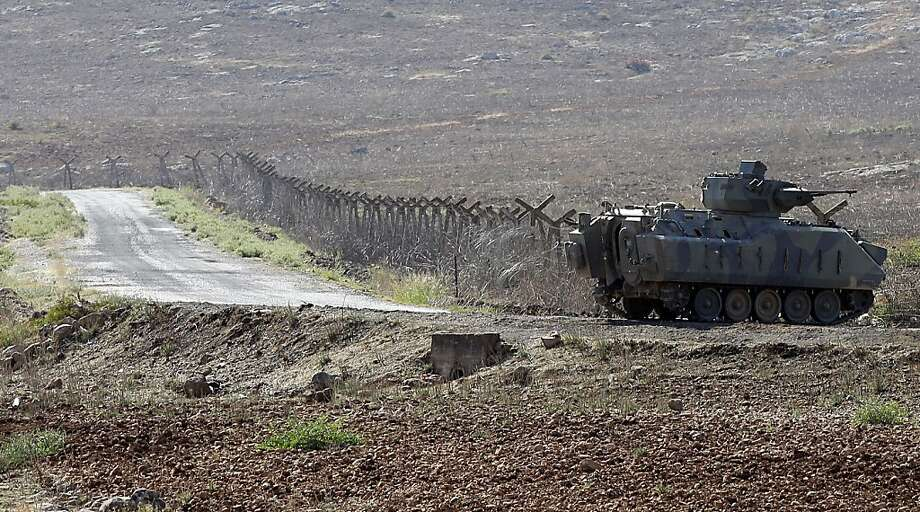 A Turkish tank stands near a fence of the Turkish-Syrian border near Cilvegozu, Turkey, Saturday, Sept. 7, 2013. European foreign ministers meeting with U.S. Secretary of State John Kerry are expected to urge the United States to hold off any military action in Syria until U.N. inspectors report on the alleged use of chemical weapons. On Saturday, Kerry and about 15 European foreign ministers attended an informal meeting of the European Union in Vilnius, Lithuania. (AP Photo/Gregorio Borgia) Photo: Gregorio Borgia, Associated Press