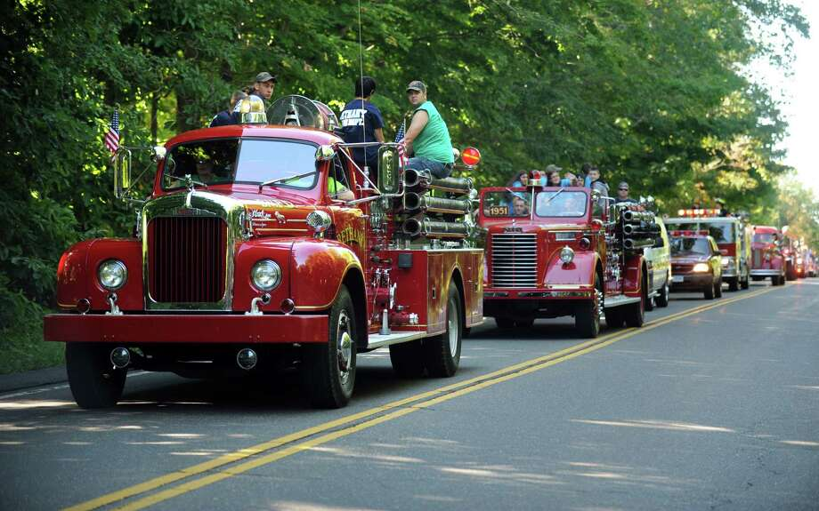 A parade of fire vehicles moves down North Street to kick off the 42nd Annual Engine 260 Antique Fire Apparatus Show & Muster at Eisenhower Park in Milford, Conn. Saturday, Sept. 7, 2013. Photo: Autumn Driscoll / Connecticut Post