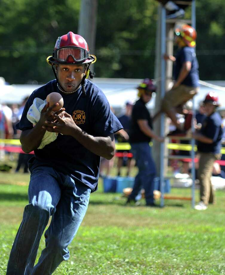 Junior firefighter Latique Alston, 17, of Ansonia, saves the baby during a timed competition at the 42nd Annual Engine 260 Antique Fire Apparatus Show & Muster at Eisenhower Park in Milford, Conn. Saturday, Sept. 7, 2013. Photo: Autumn Driscoll / Connecticut Post