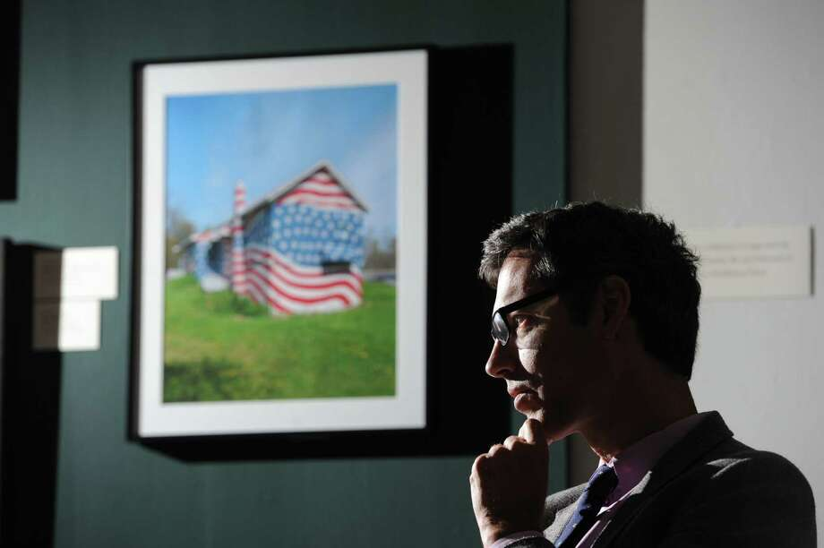 "Darien native Robert Carley, an artist and photographer, with his photographs of American Flags at the Bruce Museum in Greenwich, Saturday, Sept. 7, 2013. After Carley witnessed the Twin Towers collapse from his third floor window in Stamford on 9/11, he has made it his quest to capture the American spirit by photographing the American Flag. Carley's exhibition, ""Flags Across America,"" is featured at the Bruce Museum until Sept. 22. Photo: Bob Luckey / Greenwich Time"