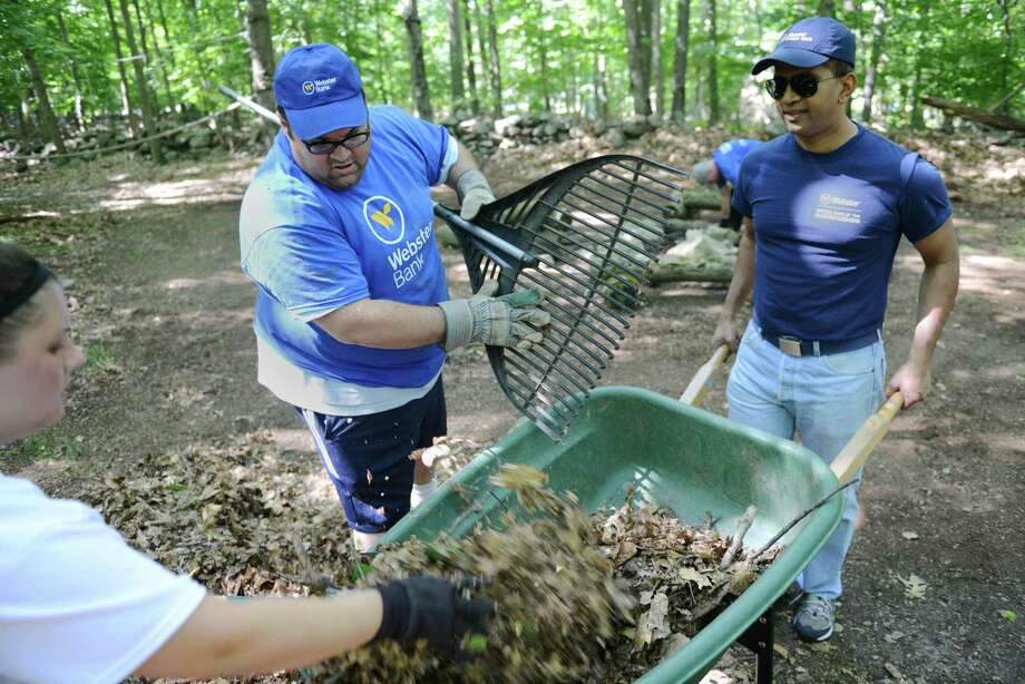 Melanie Raslen, of Newtown, and Steve Macchiarolo, of Naugatuck, collect leaves as Nitin Mhatre, of Wilton, mans the wheelbarrow during the Day of Caring, sponsored by the United Way and Webster Bank, at the Cullens Youth Association in Newtown, Conn. on Saturday, Sept. 7, 2013.  Volunteers did various renovations to the 20-acre facility, including painting, cleaning and clearing brush from the amphitheater and campsites. Photo: Tyler Sizemore / The News-Times