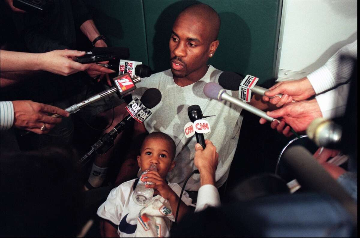 Sonics guard Gary Payton talks with reporters as his son Gary Payton Jr. looks on after a 1996 practice.