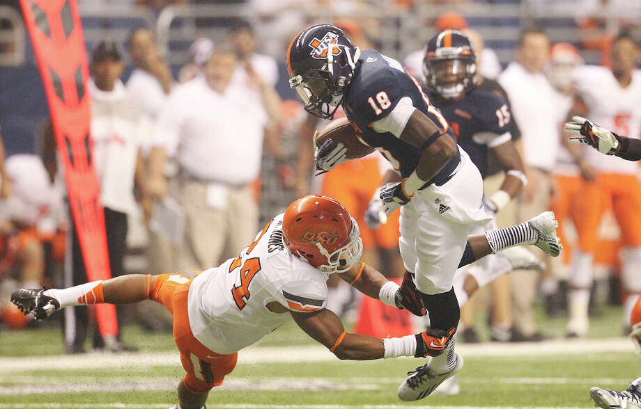 UTSA's Kenny Harrison (18) gets tripped up by Oklahoma State's Miketavius Jones (24) on a kick return in the second half at the Alamodome on Saturday, Sept. 7, 2013. OSU defeated UTSA, 56-35. Photo: Kin Man Hui, San Antonio Express-News / ©2013 San Antonio Express-News