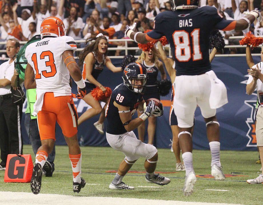 UTSA's Aaron Grubb (88) scores a touchdown against Oklahoma State's Jordan Sterns (13) in the second half at the Alamodome on Saturday, Sept. 7, 2013. OSU defeated UTSA, 56-35. Photo: Kin Man Hui, San Antonio Express-News / ©2013 San Antonio Express-News