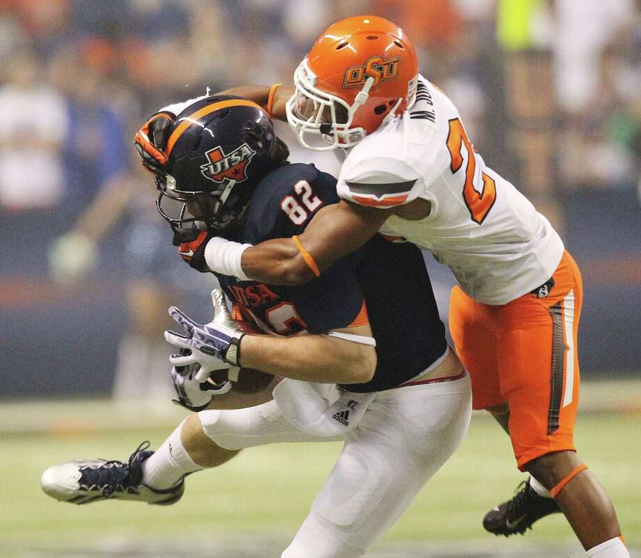 UTSA's David Morgan makes a catch against Oklahoma State's Miketavius Jones (24) in the second half at the Alamodome on Saturday, Sept. 7, 2013. OSU defeated UTSA, 56-35. Photo: Kin Man Hui, San Antonio Express-News / ©2013 San Antonio Express-News