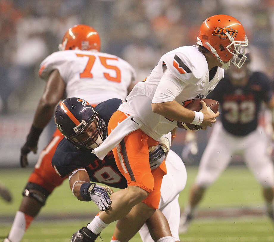 UTSA's Codie Brooks gets a sack against Oklahoma State's Clint Chelf (10) in the second half at the Alamodome on Saturday, Sept. 7, 2013. OSU defeated UTSA, 56-35. Photo: Kin Man Hui, San Antonio Express-News / ©2013 San Antonio Express-News
