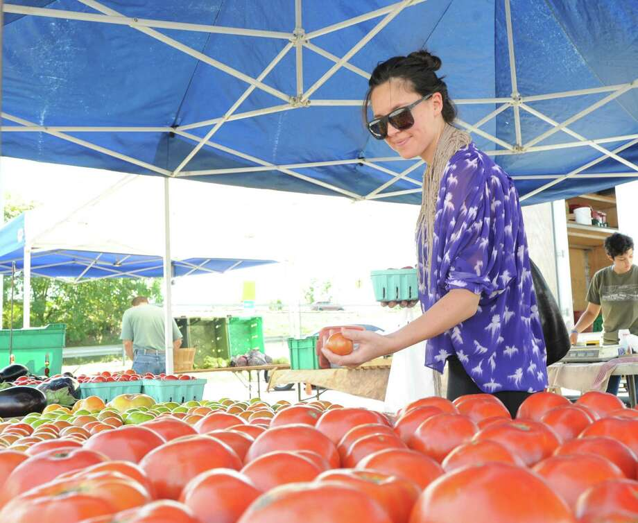 """Ellen Rowett of Greenwich shops for tomatoes during the Greenwich Farmers Market in the Horseneck public parking lot, Saturday, Sept. 7, 2013. Market Master, Judy Waldeyer of Stratford, said the market will be in business every Saturday from 9:30 a.m. to 1 p.m., including the Saturday before Thanksgiving. The Saturday of Thanksgiving the market moves to the Arch Street Teen Center and is in business every Saturday at the usual hours """"until the produce runs out,"""" she said. Photo: Bob Luckey / Greenwich Time"""