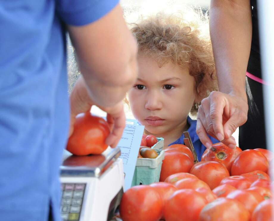 "Dante Parrotta, 3, of Greenwich, watches as a beefstake tomato is weighed on a scale during the Greenwich Farmers Market in the Horseneck public parking lot, Saturday, Sept. 7, 2013. Market Master, Judy Waldeyer of Stratford, said the market will be in business every Saturday from 9:30 a.m. to 1 p.m., including the Saturday before Thanksgiving. The Saturday of Thanksgiving the market moves to the Arch Street Teen Center and is in business every Saturday thereafter at the usual hours ""until the produce runs out,"" she said. Photo: Bob Luckey / Greenwich Time"