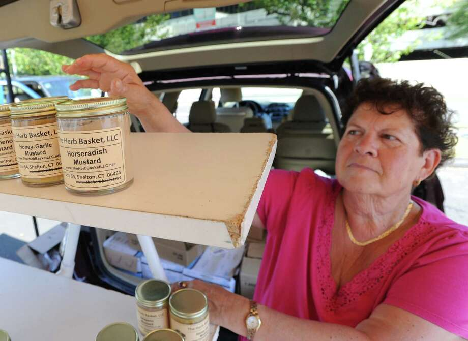 "Judy Waldeyer of Stratford packs up Horseradish Mustard that she was selling during the Greenwich Farmers Market in the Horseneck public parking lot, Saturday, Sept. 7, 2013. Waldeyer, the market master, said the market will be in business every Saturday from 9:30 a.m. to 1 p.m., including the Saturday before Thanksgiving. The Saturday of Thanksgiving the market moves to the Arch Street Teen Center and is in business every Saturday at the usual hours ""until the produce runs out,"" she said. Photo: Bob Luckey / Greenwich Time"