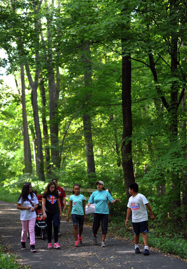 Cynthia Usedo, a teacher and counselor with the Pathfinders Club at Spanish Orion Seventh-day Adventist Church in Bridgeport, second from right, teachs several youths in the club about nature with emphasis on God and creation, during a nature hike at Old Mine Park in Trumbull, Conn. on Saturday September 7, 2013. The Pathfinders Club is an international club for youth sponsored by the Seventh-day Adventist Church and in Connecticut, Massachussetts, and Rhode Island there are 45 clubs with over 1200 members. Members from left to right are Whitney Lopez, 11, Sabina Hughes, 11, Olivia Sarmiento, 10, Usedo, and Saul Aguilar, 12. There were about 30 kids who came to the park and broke up into small groups with other instructors to learn about nature, the environment, good stewardship of it, and other topics with a spiritual theme. For more information about the Pathfinders organization: http://www.pathfindersonline.org/ Photo: Christian Abraham / Connecticut Post