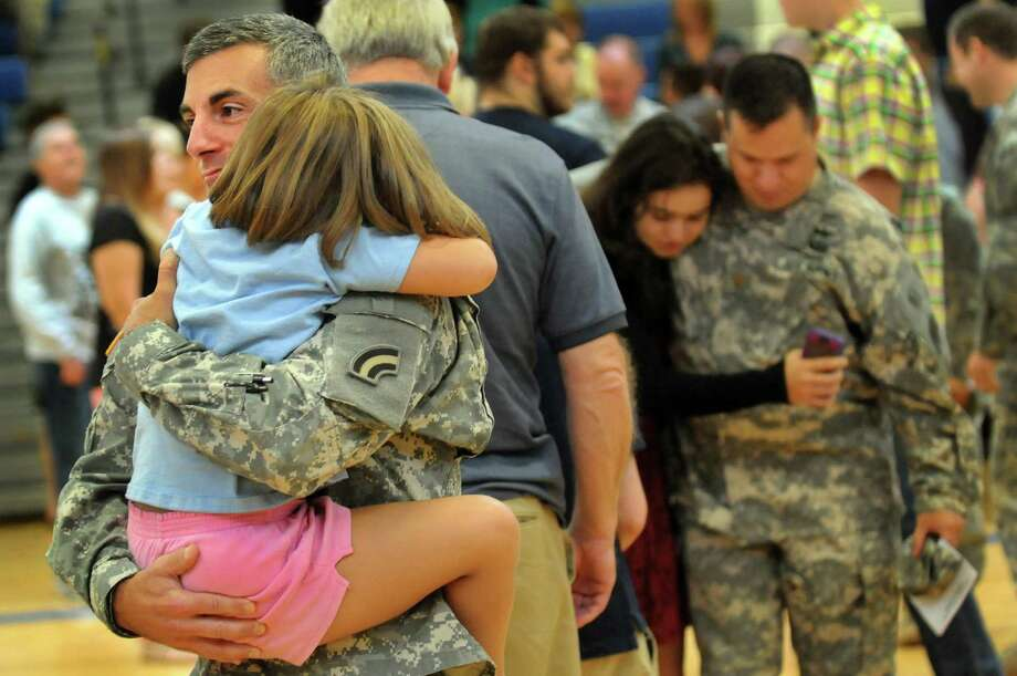 2nd Lt. Matthew Williams of Ballston Spa, left, carries his daughter Mia Williams, 5, following the departure ceremony for the 42nd Combat Aviation Brigade on Saturday, Sept. 7, 2013, at Shaker High in Latham, N.Y. Williams is among the soldiers who will deploy to Fort Hood, Texas for training and then to Kuwait, where they will provide Army aviation support to American forces stationed there. (Cindy Schultz / Times Union) Photo: Cindy Schultz / 00023780A