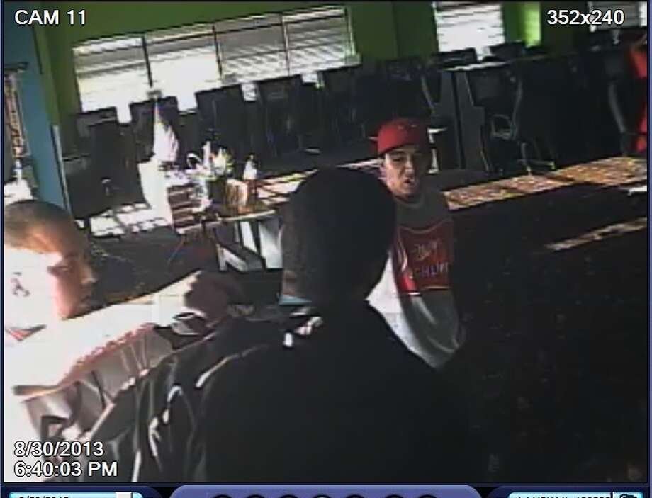 Authorities want to identify and arrest this man (without a hat) in connection with a game room robbery and shooting death Aug. 30 in southeast Houston. Photo: Houston Police Department