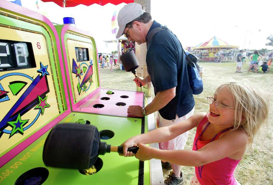 Sofia Senecal, 8, and her father, Paul, play Whac-a-Mole during the Norwalk Seaport Association's 37th annual oyster festival on Saturday, September 7, 2013. Photo: Lindsay Perry / Stamford Advocate