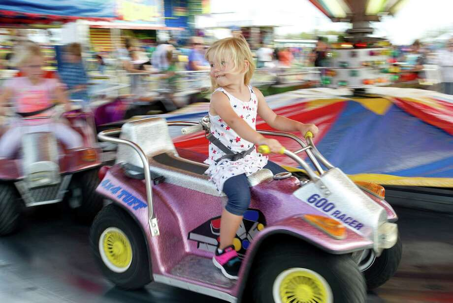 Cora Couch, 2, takes a ride during the Norwalk Seaport Association's 37th annual oyster festival on Saturday, September 7, 2013. Photo: Lindsay Perry / Stamford Advocate