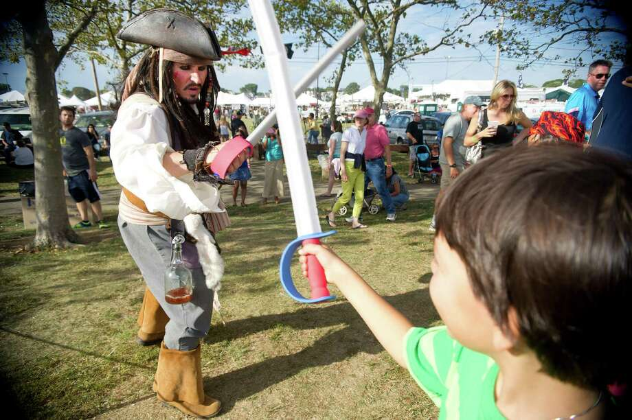 Pirate Michael Lopresti teaches Wesley Khakoo, 9, swordfighting moves with foam swords during the Norwalk Seaport Association's 37th annual oyster festival on Saturday, September 7, 2013. Photo: Lindsay Perry / Stamford Advocate