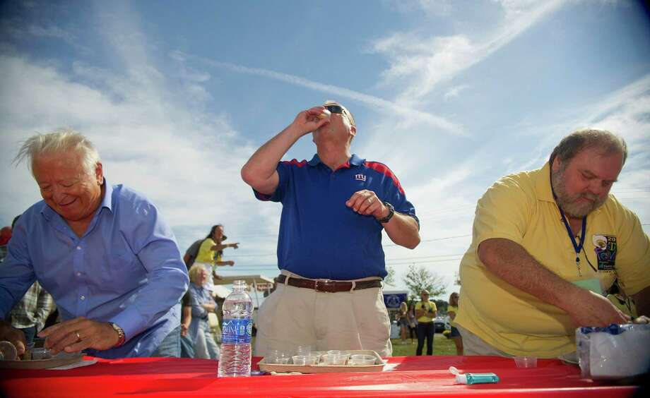 From left, Norwalk Mayor Richard Moccia, Police Chief Tom Kulhawic and city council member Doug Hempstead compete in the Celebrity Slurp-off oyster-eating contest during the Norwalk Seaport Association's 37th annual oyster festival on Saturday, September 7, 2013. Photo: Lindsay Perry / Stamford Advocate