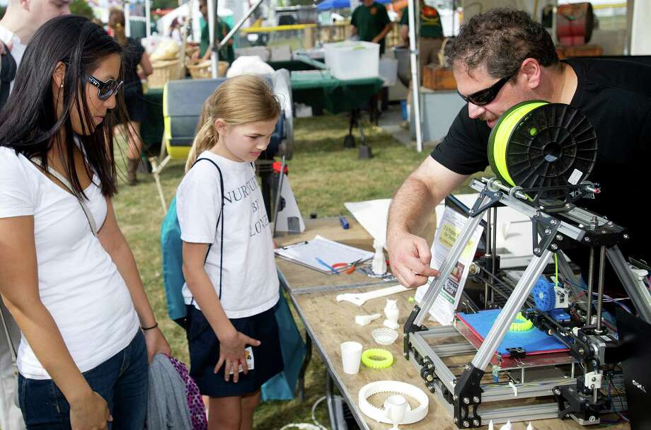 Festival attendees take a look at a 3-d printer and other electronics at the Fairfield County Maker's Guild booth during the Norwalk Seaport Association's 37th annual oyster festival on Saturday, September 7, 2013. Photo: Lindsay Perry / Stamford Advocate