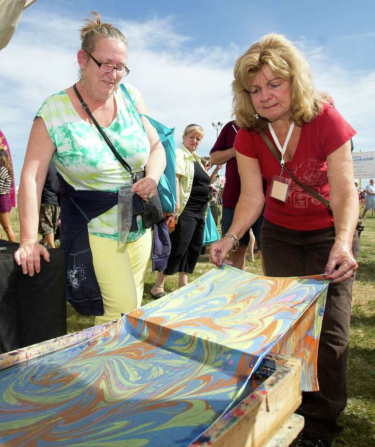 Cheryl Williams, left, makes a silk scarf at the Shibumi booth with Patricia DiSantis, right, during the Norwalk Seaport Association's 37th annual oyster festival on Saturday, September 7, 2013. Photo: Lindsay Perry / Stamford Advocate