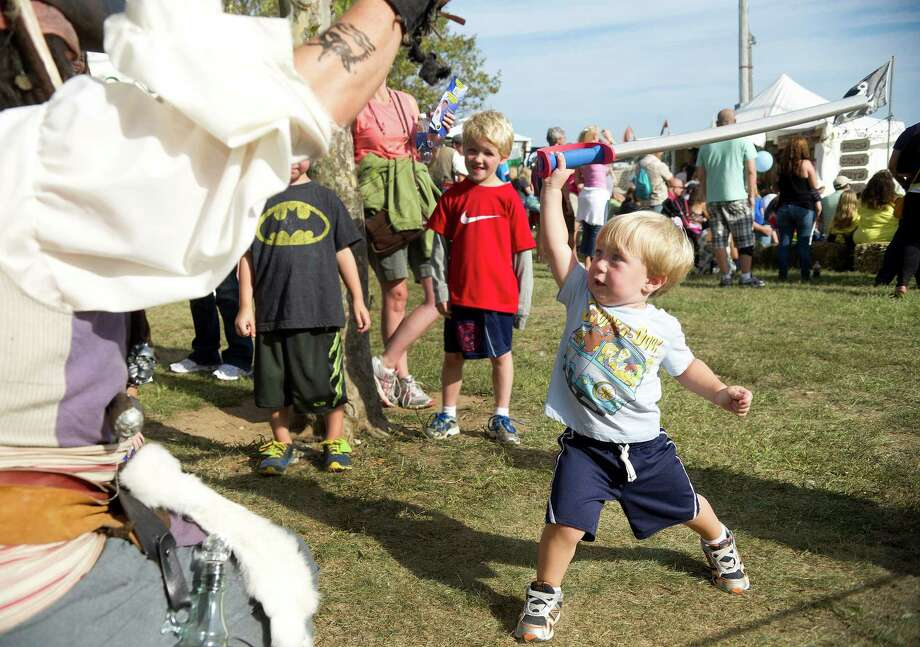Pirate Michael Lopresti teaches Luke Baker, 2, swordfighting moves with foam swords during the Norwalk Seaport Association's 37th annual oyster festival on Saturday, September 7, 2013. Photo: Lindsay Perry / Stamford Advocate