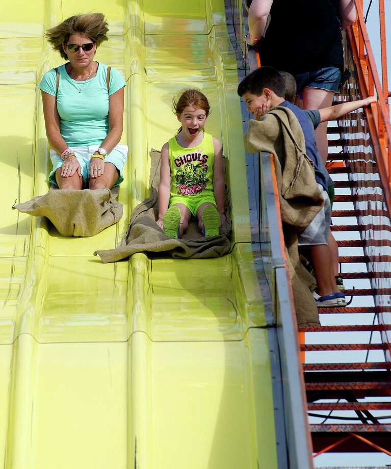 Michelle Hewitt and her daughter, Hayley, 6, go down the slide during the Norwalk Seaport Association's 37th annual oyster festival on Saturday, September 7, 2013. Photo: Lindsay Perry / Stamford Advocate