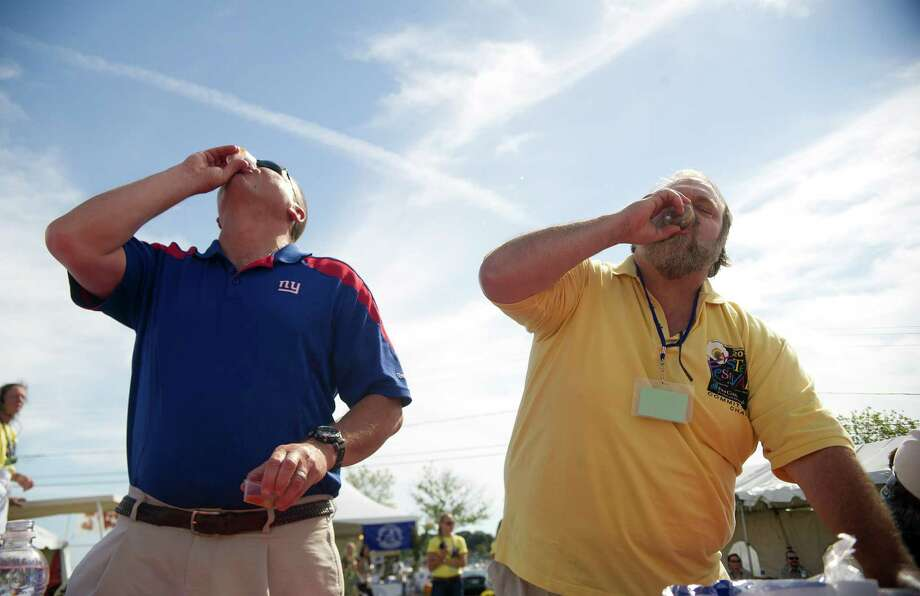 From left, Norwalk Police Chief Tom Kulhawic and city council member Doug Hempstead compete in the Celebrity Slurp-off oyster-eating contest during the Norwalk Seaport Association's 37th annual oyster festival on Saturday, September 7, 2013. Photo: Lindsay Perry / Stamford Advocate