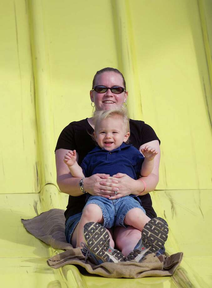Sabrina Spence and her son, Tyler, 1, go down the slide during the Norwalk Seaport Association's 37th annual oyster festival on Saturday, September 7, 2013. Photo: Lindsay Perry / Stamford Advocate