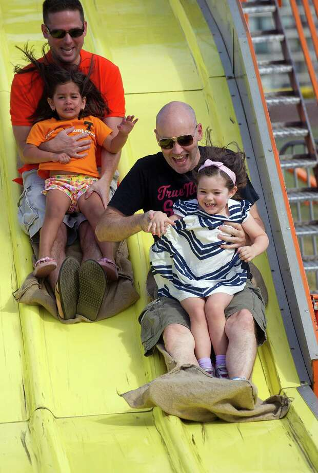Rob Kavanaugh and his daugther, Chloe, 3, right, ride the slide during the Norwalk Seaport Association's 37th annual oyster festival on Saturday, September 7, 2013. Photo: Lindsay Perry / Stamford Advocate