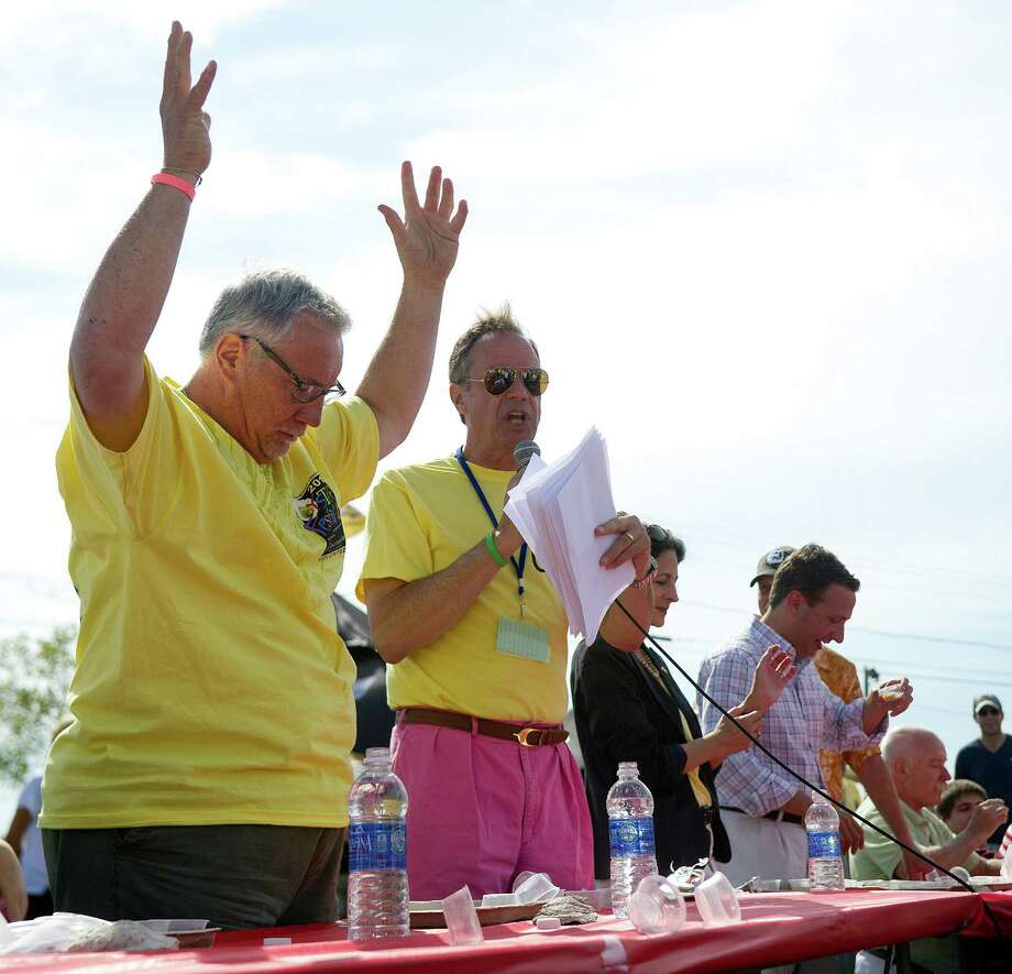 Norwalk Town Clerk Rick McQuaid raises his arms in victory as he wins the Celebrity Slurp-off oyster-eating contest during the Norwalk Seaport Association's 37th annual oyster festival on Saturday, September 7, 2013. Photo: Lindsay Perry / Stamford Advocate