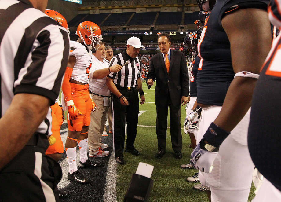 Former city mayor Henry Cisneros performs the honorary coin toss for the UTSA - Oklahoma State game at the Alamodome on Saturday, Sept. 7, 2013. Photo: Kin Man Hui, San Antonio Express-News / ©2013 San Antonio Express-News