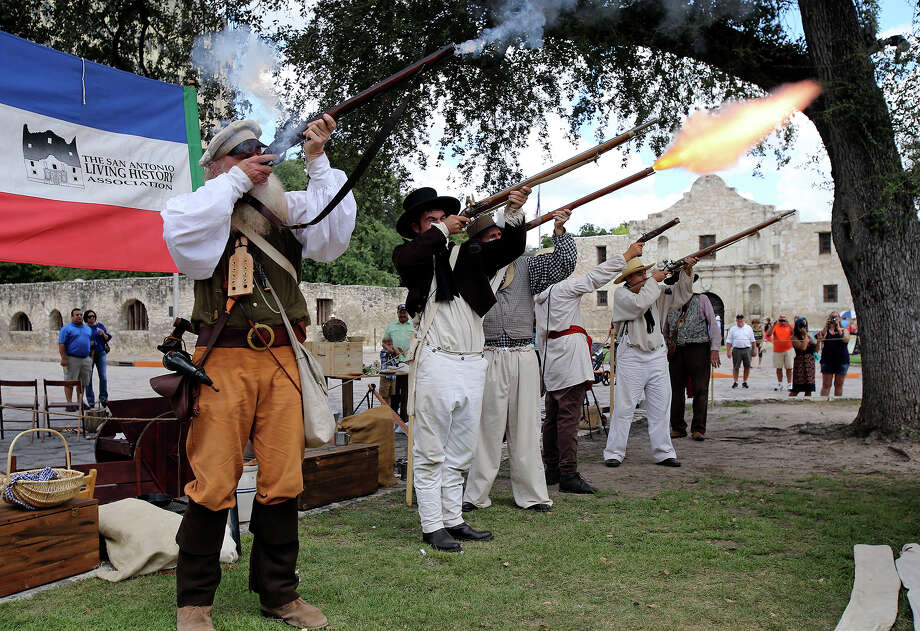 The San Antonio Living History Association fires a rifle blast in front of the Alamo as the Save Texas History symposium is hosted by theTexas General Land Office on September 7,  2013. Photo: Tom Reel, San Antonio Express-News