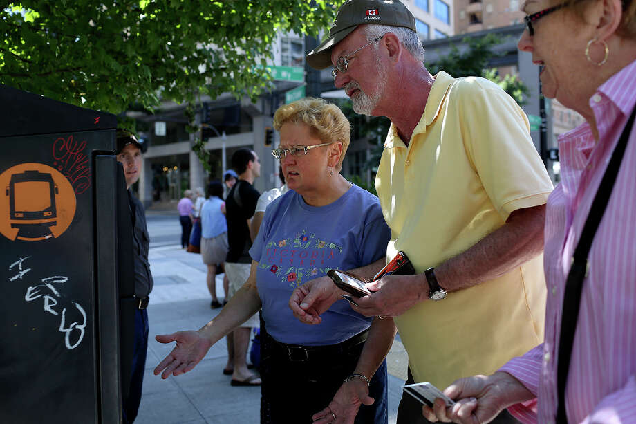 Gary Crow and Judy Crow of Bloomington, IN and Sherry Stevens, right, of Seattle, try to figure out how to buy a ticket to ride the Seattle Streetcar in Seattle on July 8, 2013. Stevens works as a tour guide and was riding the streetcar prior to instructing travelers staying downtown to use it. Photo: Lisa Krantz, San Antonio Express-News / San Antonio Express-News