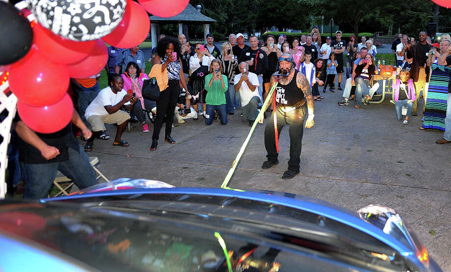 """Nick """"Batso"""" Maccharoli pulls his Nissan Leaf with his neck as he celebrates his 80th birthday party with family and friends at Boothe Memorial Park in Stratfordl, Conn. on Saturday September 7, 2013. September 7th is also his wedding anniversary - he and his wife Elly, were married in Boothe Park in 1985. Photo: Christian Abraham / Connecticut Post"""